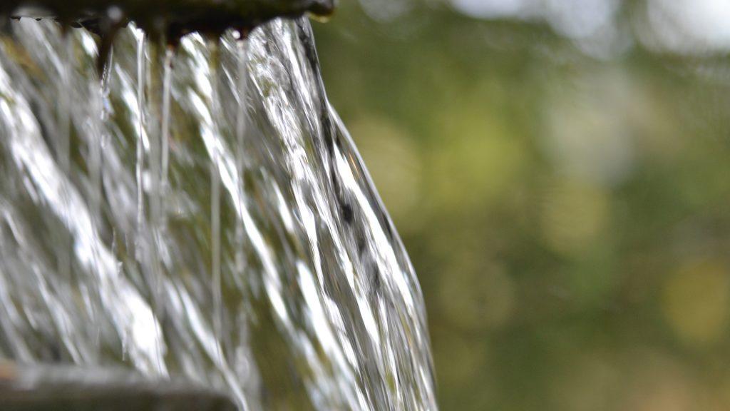 Alas virtaavaa, kirkasta vettä, joka heijastaa valoa.