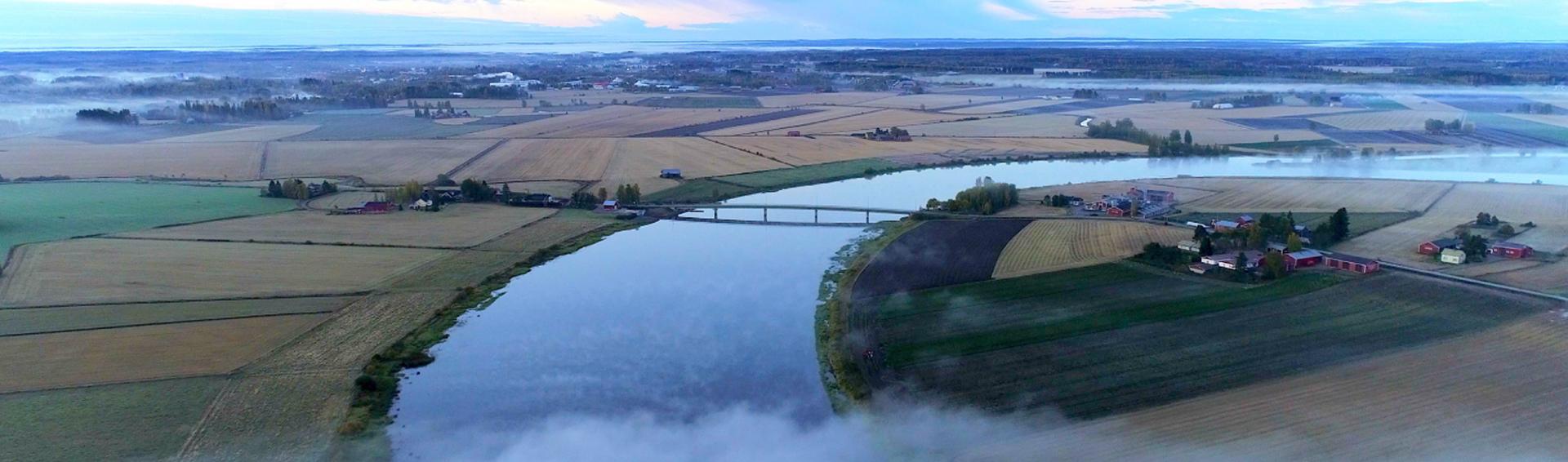 Peltojen keskellä virtaa sininen joki, joka tekee mutkan oikealle. Joen yli kulkee silta.