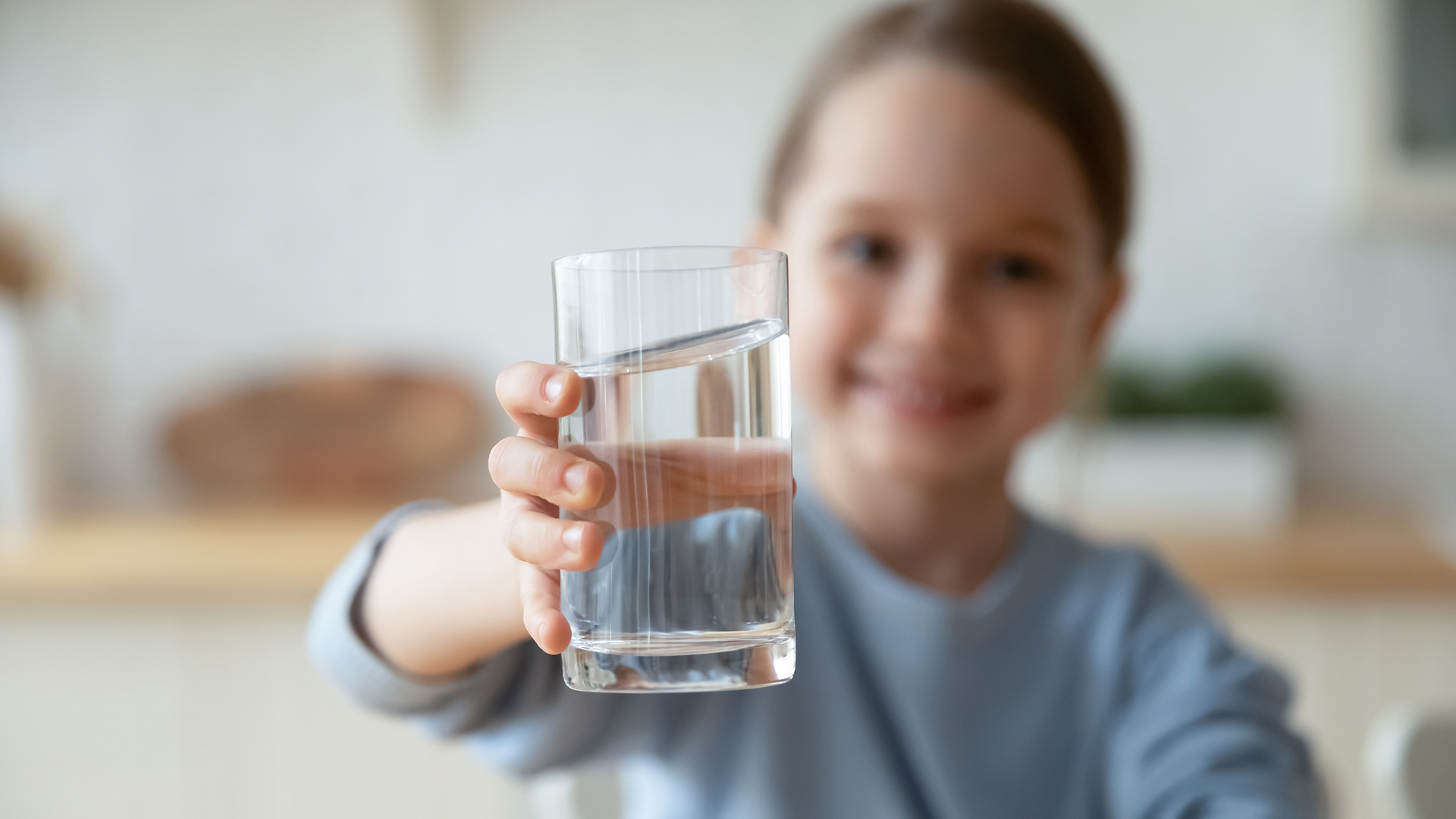 Hymyilevä lapsi kohottaa vesilasia, jossa on kirkasta vettä, kuvaajaa kohti.
