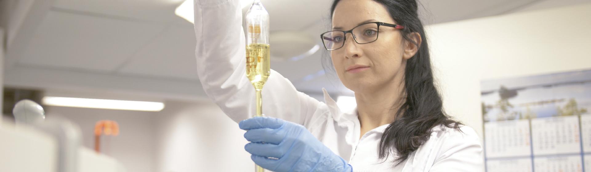 Tutkija tarkastelee laboratoriossa nestenäytettä, joka on läpinäkyvässä, muovisessa pussissa. Pussin neste on kellertävää.